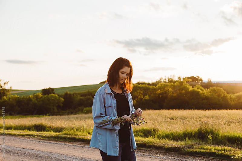 Beautiful woman standing on countryside road at dusk by Carey Shaw for Stocksy United