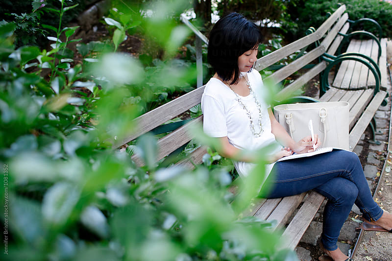 lovely woman sitting on park bench, journaling in notebook  by Jennifer Brister for Stocksy United