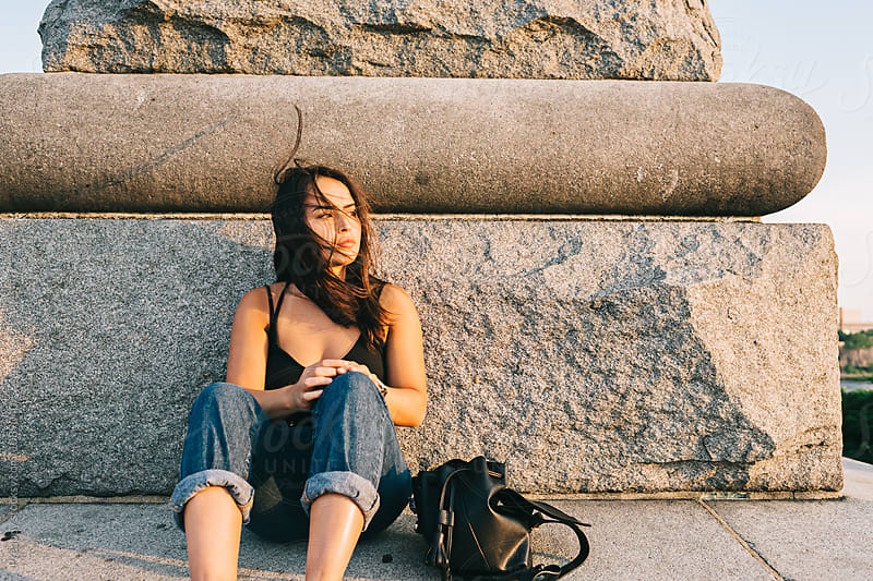 Pensive teen sitting on stone monument alone by Preappy for Stocksy United