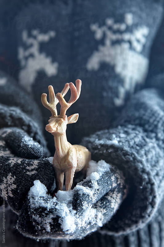 Mitten hands with snow holding a wooden reindeer by Sandra Cunningham for Stocksy United