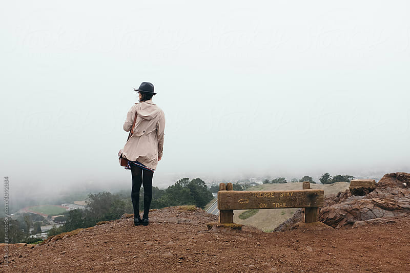 rear view of tourist in hat and coat on top of Twin Peaks viewpoint by Lucas Saugen for Stocksy United