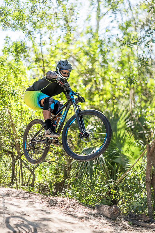 Mountain Biker Catches Air on Trail Jumps by suzanne clements for Stocksy United