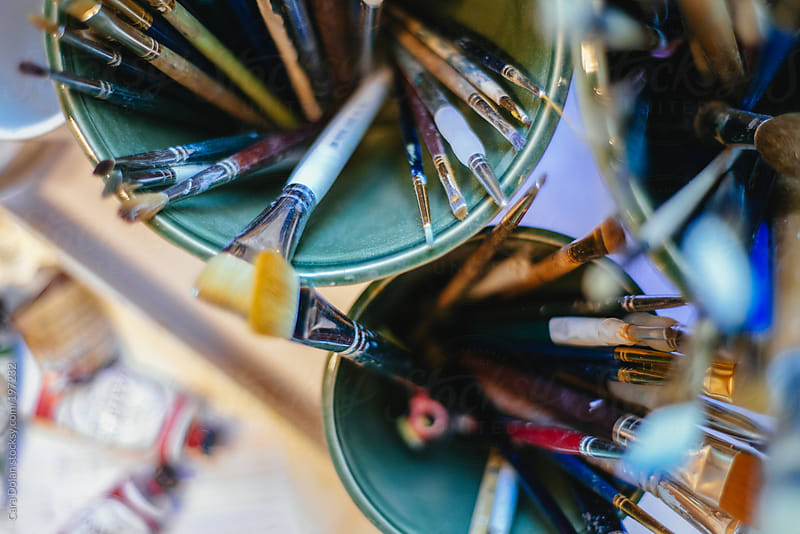 Paintbrushes inside containers in an artist's studio by Cara Dolan for Stocksy United