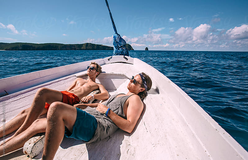 Two young friends relaxing in the sun on a boat at sea by Soren Egeberg for Stocksy United