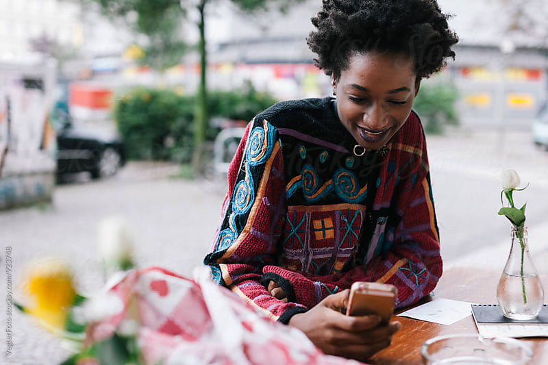 Black Woman checking messages on phone by VegterFoto for Stocksy United