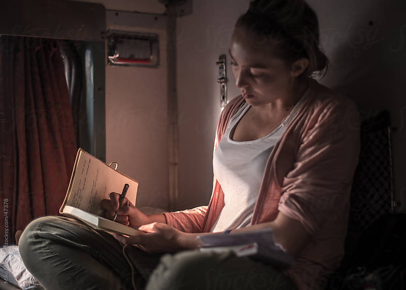 A young woman traveller updating her daily journal while on a train by Mike Marlowe for Stocksy United