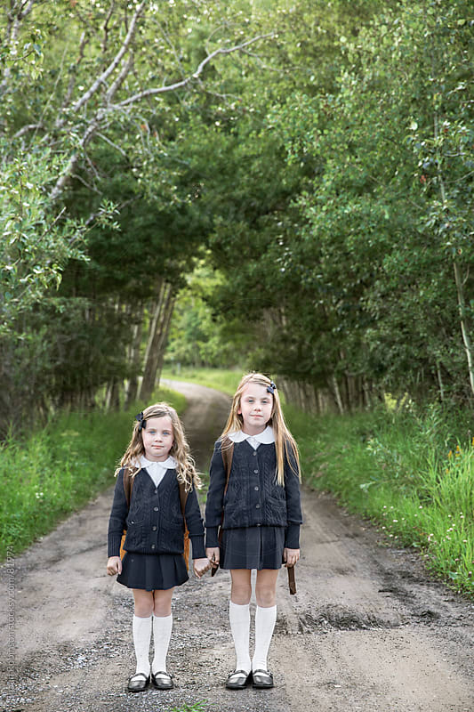 two girls standing on a gravel road holding hands by Shaun Robinson for Stocksy United