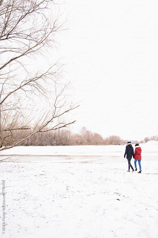 Photo of couple walking down the winter snowed coast by T-REX & Flower for Stocksy United