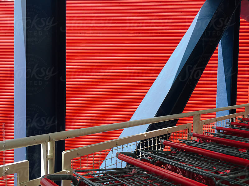 Row and shopping carts and vivid red wall in background by Paul Edmondson for Stocksy United