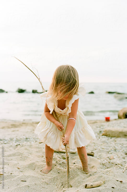 little girl playing in sand with stick by Maria Manco for Stocksy United