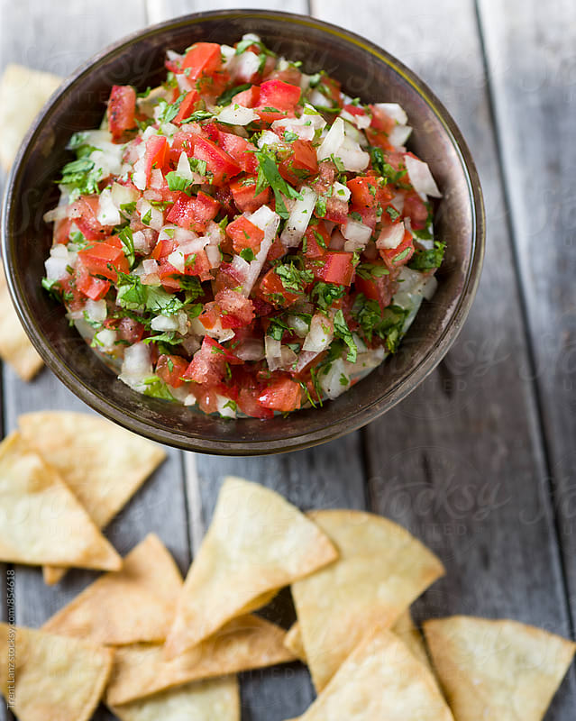 Homemade nacho tortilla chips and salsa ingredients by Trent Lanz for Stocksy United