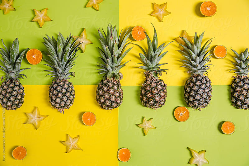 Feeling tropical - pineapples and star fruit on colourful background by Jovo Jovanovic for Stocksy United