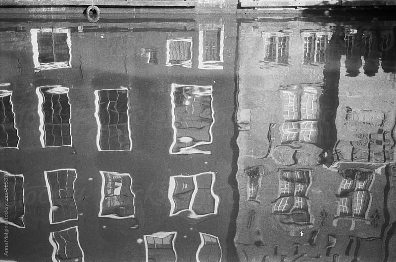 A black and white film photo of reflection in the Amsterdam canal  by Anna Malgina for Stocksy United