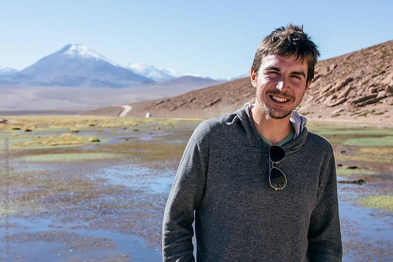 Young happy man portrait on adventure travel in mountain landscape by Alejandro Moreno de Carlos for Stocksy United