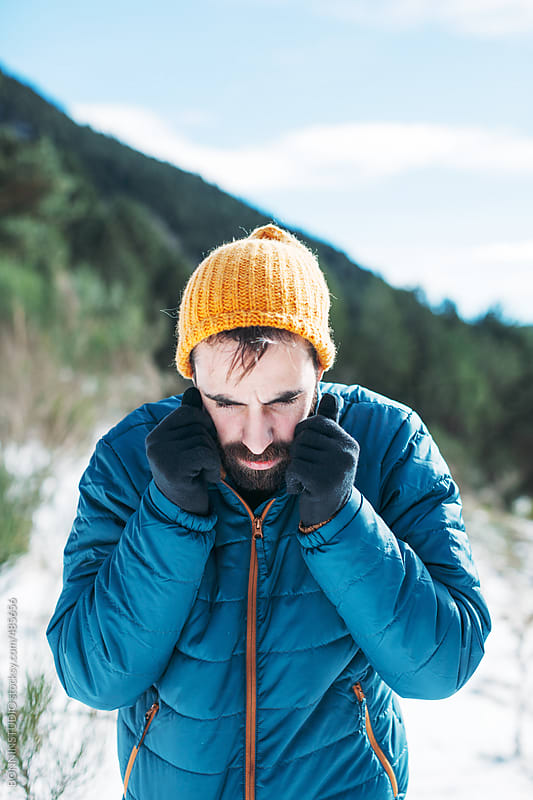 Young man standing on a cold snowy day. by BONNINSTUDIO for Stocksy United