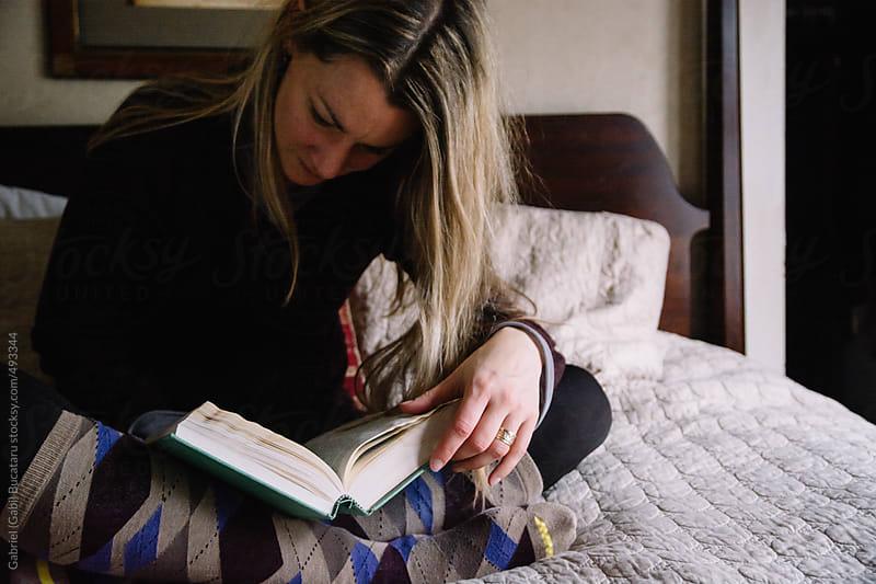 Blonde woman sitting on a bed reading a book by Gabriel (Gabi) Bucataru for Stocksy United