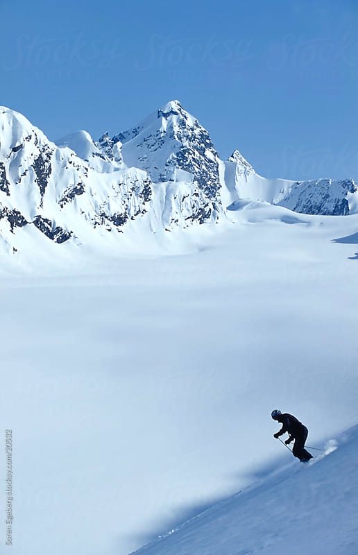 Adult male skiing a powder slope in the mountains of Alaska by Soren Egeberg for Stocksy United