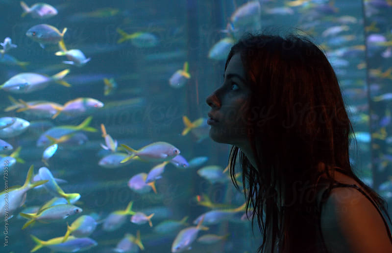 Portrait of a girl in front of an aquarium with fish by Yury Goryanoy for Stocksy United