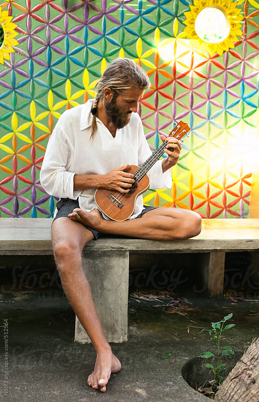 Hippie man playing ukulele in front of colorful flower of life wall by Nabi Tang for Stocksy United