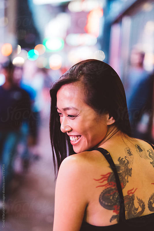 Asian woman smiling in Time Square at night by Good Vibrations Images for Stocksy United