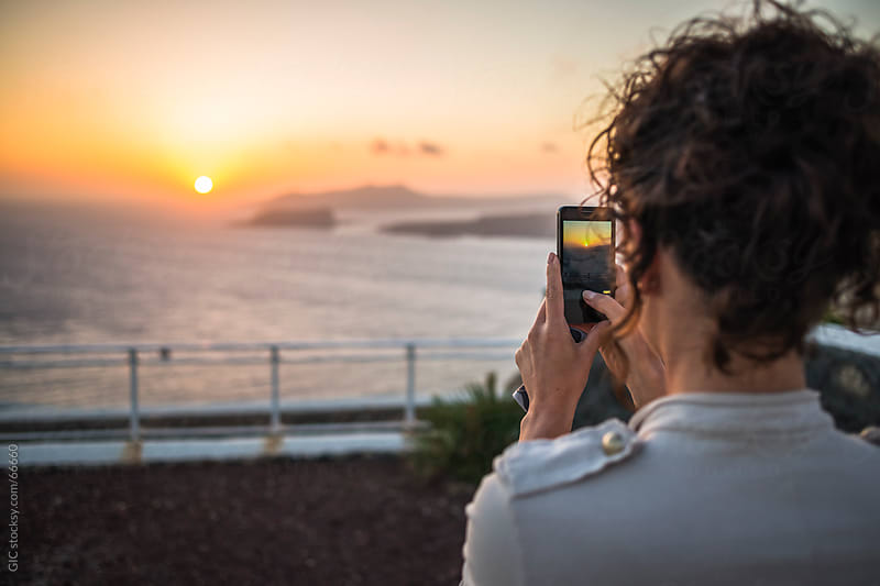 Woman taking a picture of famous Santorini sunset by Simone Becchetti for Stocksy United