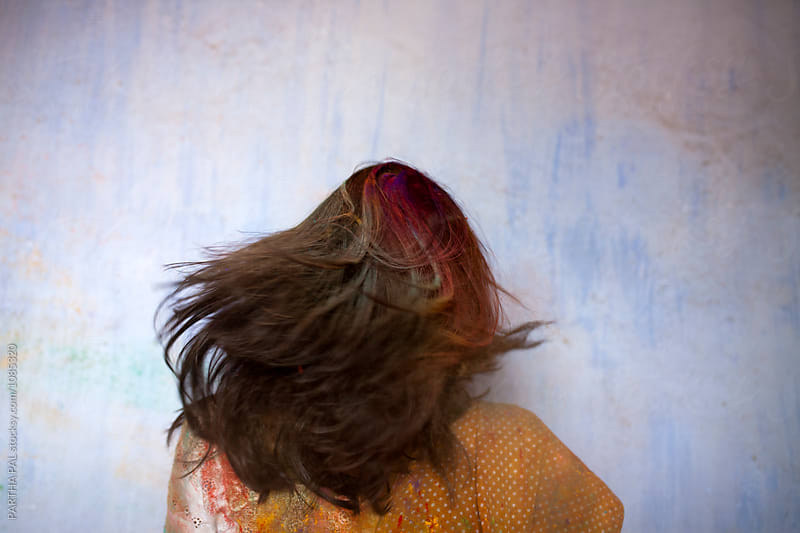 Indian Woman shaking head and making fun with spray color powder during Holi Festival by PARTHA PAL for Stocksy United