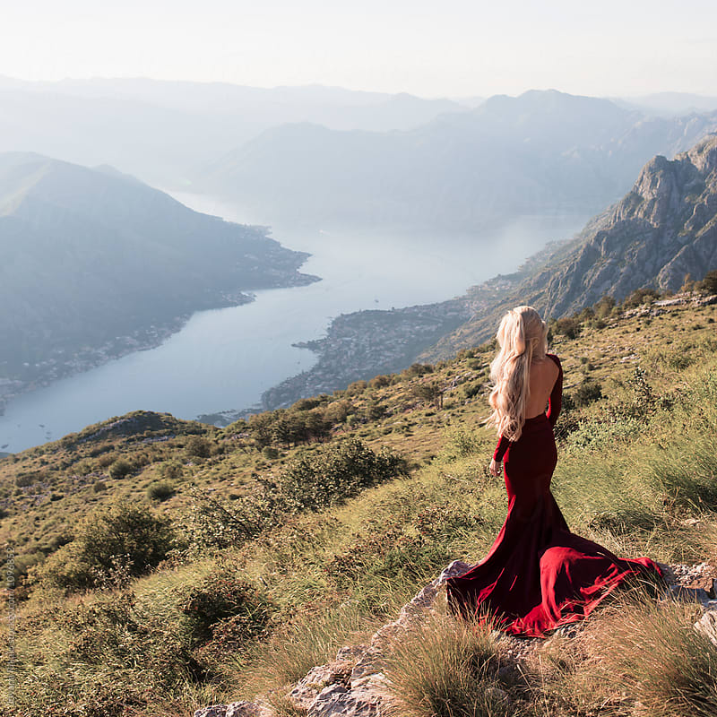 Young woman in a red dress standing on the hill by Jovana Rikalo for Stocksy United