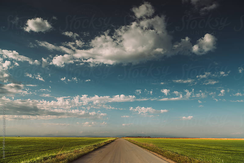 rural road with a fantastic sky with mystic clouds by Javier Pardina for Stocksy United