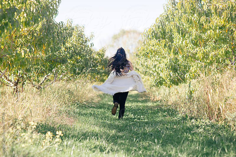 Brunette woman runs through Orchard pathway on farm by HOWL for Stocksy United
