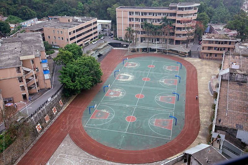 Aerial view of a school's basketball and oval track and field facilities by Lawrence del Mundo for Stocksy United
