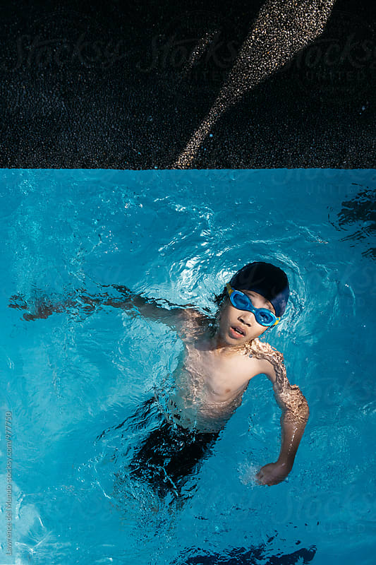 Top view action shot of a young swimmer doing backstroke about to finish by Lawrence del Mundo for Stocksy United