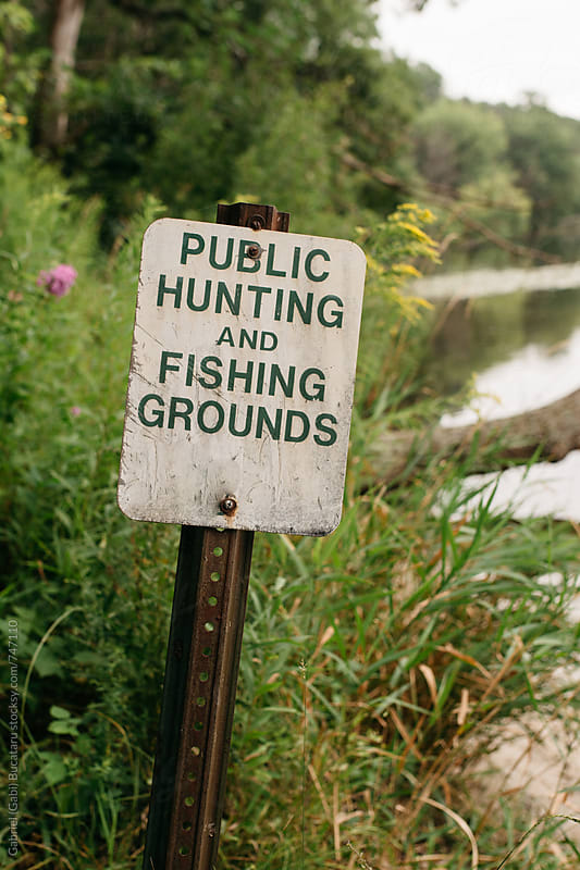 Public hunting and fishing groungs sign by a lake by Gabriel (Gabi) Bucataru for Stocksy United