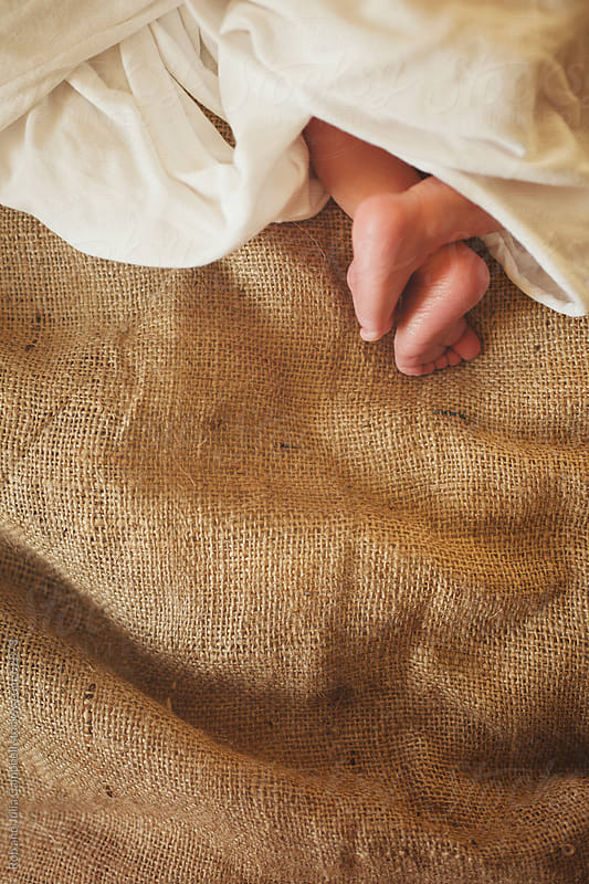Newborn baby boy sleeping on burlap blanket by Rob and Julia Campbell for Stocksy United