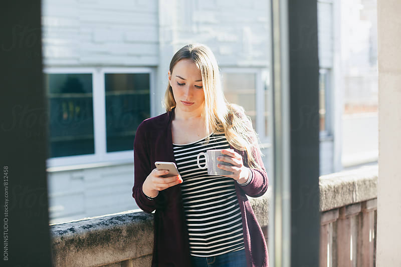 Blonde woman taking a break and using her smartphone in the terrace. by BONNINSTUDIO for Stocksy United