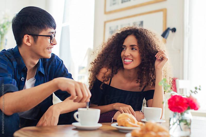 Happy trendy couple having breakfast in a coffee shop. by BONNINSTUDIO for Stocksy United