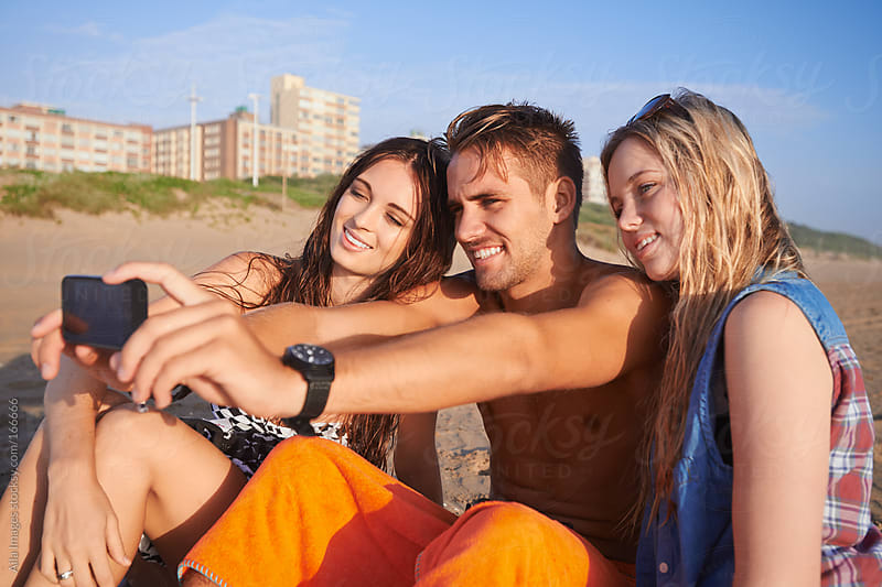 Three Friends on the Beach taking Selfies by Aila Images for Stocksy United