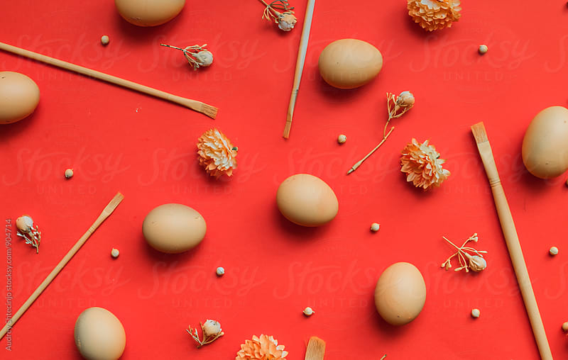 Easter eggs on orange/red background. by Audrey Shtecinjo for Stocksy United