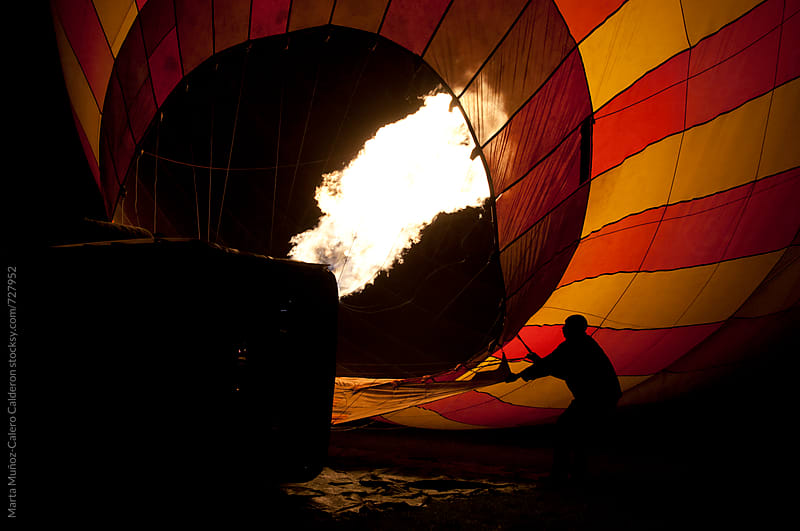 Men holding a rope wile flames burst out in a hot air balloon  by Marta Muñoz-Calero Calderon for Stocksy United