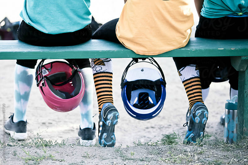 View from the back of a girl's softball bench - fun socks and pink helmets by Carolyn Lagattuta for Stocksy United