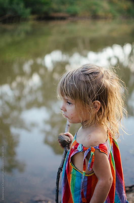 Young girl playing at river by Dominique Chapman for Stocksy United