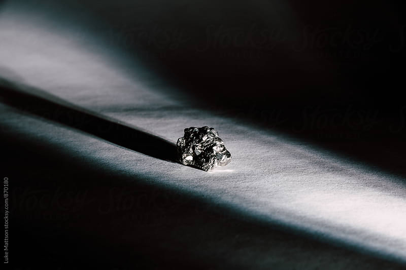 Pyrite, Commonly Known As Fool's Gold, Illuminated By Beam Of Light by Luke Mattson for Stocksy United