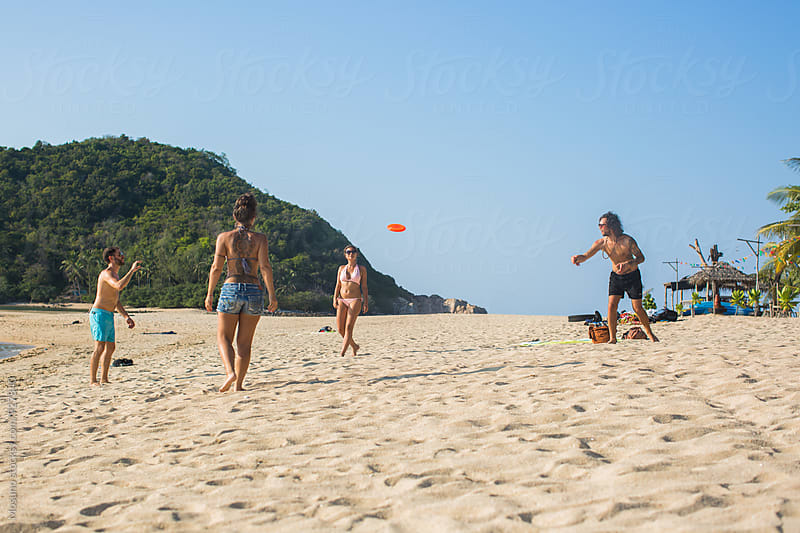 Friends Playing Frisbee on the Beach by Mosuno for Stocksy United