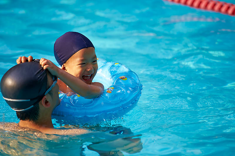 happy asian kid in swimming pool by cuiyan Liu for Stocksy United