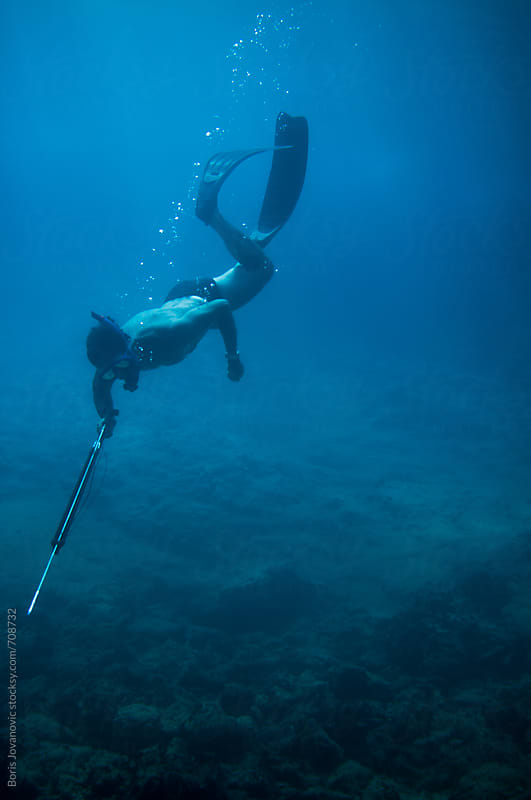 Diver diving and looking for a fish to hunt by Boris Jovanovic for Stocksy United