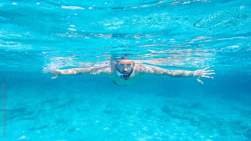 Young man diving in crystal clear waters by ACALU Studio for Stocksy United