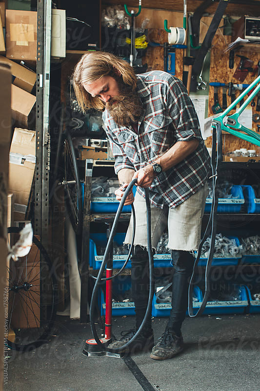 Blond Hipster Mechanic Pumping Bike Tube in Bright Workshop by Julien L. Balmer for Stocksy United