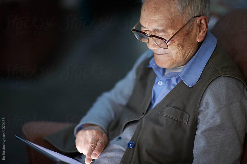 senior asian man using tablet indoor by Bo Bo for Stocksy United