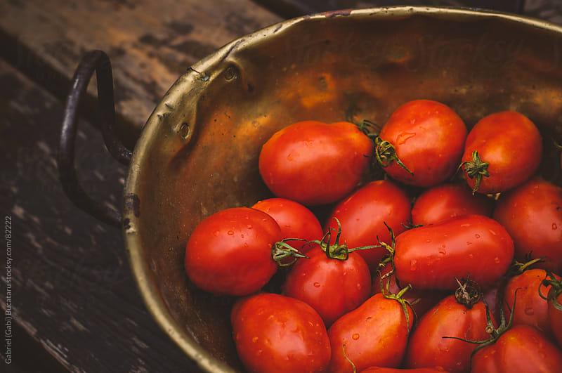 an antique brass bowl with fresh Roma tomatoes by Gabriel (Gabi) Bucataru for Stocksy United