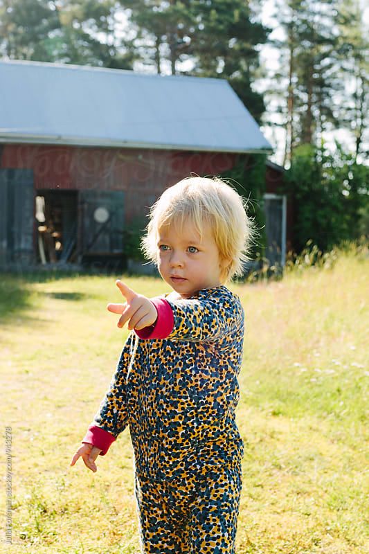 A little girl in bright sunshine points at something out of sight. In the background is a large Scandinavian barn. by Julia Forsman for Stocksy United