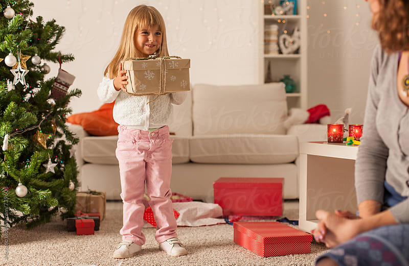 Cute Little Girl Opening Christmas Present by Mosuno for Stocksy United